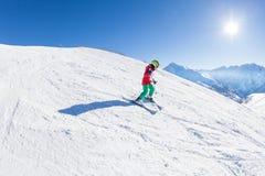 Pequeño esquiador que camina abajo de la colina en el día soleado Fotos de archivo libres de regalías