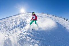 Pequeño esquiador que camina abajo de la colina en montañas Fotos de archivo libres de regalías