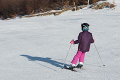 Pequeño esquiador que compite con en nieve Fotos de archivo