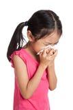 Pequeño estornudo asiático de la muchacha con el papel de la servilleta Imágenes de archivo libres de regalías