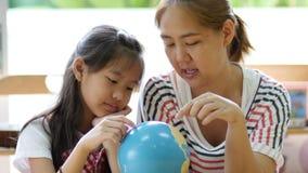 Pequeño estudiante asiático que mira el globo metrajes