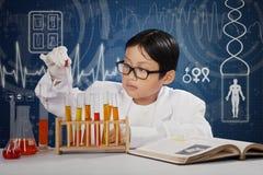 Pequeño estudiante que juega el líquido químico Foto de archivo