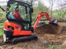 Pequeño excavador con el hombre dentro, en el trabajo que hace la charca del jardín Imagen de archivo