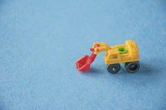 Pequeño excavador decorativo del juguete en fondo azul Foto abstracta macra Construcción, explotación minera, material de constru imagen de archivo libre de regalías