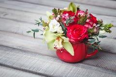 Pequeño florero rojo con el ramo de flores y de lirios en el espacio de madera de la tabla para el texto Fotografía de archivo