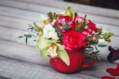 Pequeño florero rojo con el ramo de flores y de lirios en el espacio de madera de la tabla para el texto Foto de archivo libre de regalías