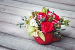 Pequeño florero rojo con el ramo de flores y de lirios en el espacio de madera de la tabla para el texto Imagen de archivo