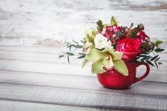 Pequeño florero rojo con el ramo de flores y de lirios en el espacio de madera de la tabla para el texto Imagen de archivo libre de regalías