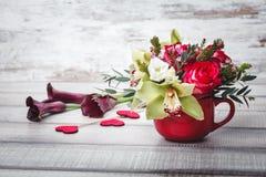 Pequeño florero rojo con el ramo de flores y de lirios en el espacio de madera de la tabla para el texto Fotografía de archivo libre de regalías