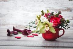 Pequeño florero rojo con el ramo de flores y de lirios en el espacio de madera de la tabla para el texto Fotos de archivo