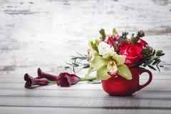 Pequeño florero rojo con el ramo de flores y de lirios en el espacio de madera de la tabla para el texto Foto de archivo