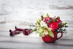 Pequeño florero rojo con el ramo de flores y de lirios en el espacio de madera de la tabla para el texto Imagenes de archivo