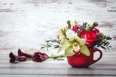 Pequeño florero rojo con el ramo de flores y de lirios en el espacio de madera de la tabla para el texto Fotos de archivo libres de regalías