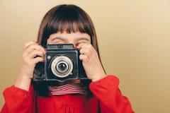 Pequeño fotógrafo retro con una cámara vieja Fotografía de archivo