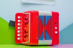 Pequeño Garmon rojo para los niños Un pequeño acordeón, armónico, instrumento musical, llaves del blanco de la reparación de la m imágenes de archivo libres de regalías