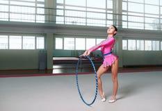 Pequeño gimnasta de sexo femenino que presenta con el aro Fotos de archivo