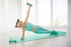 Pequeño gimnasta deportivo de la muchacha en la ropa de deportes que hace ejercicios en una estera interior fotos de archivo