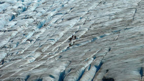 Pequeño grupo de personas que camina en un glaciar Fotografía de archivo libre de regalías