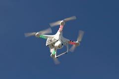 Pequeño helicóptero sin tripulación con una cámara que flota en el cielo Imagenes de archivo