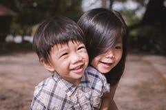 Pequeño hermano asiático lindo y hermana jovenes y alegres imagenes de archivo