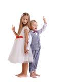 Pequeño hermano lindo, divertido y hermana aislados en un fondo blanco Niños de lujo que señalan en algo Concepto de familia Foto de archivo