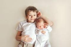 Pequeño hermano que abraza a su bebé recién nacido Niño del niño que encuentra al nuevo hermano El muchacho lindo y el bebé recié fotografía de archivo