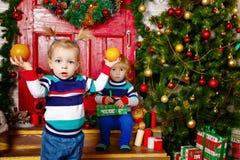 Pequeño hermano y hermana cerca del árbol de navidad Fotos de archivo