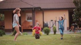 Pequeño hermano y hermana que repiten después de una más vieja hermana Baile de la familia en el patio trasero afuera en el día d metrajes