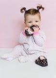 Pequeño hermoso una niña pequeña se sienta y juega con el children& x27; zapatos de s Fotografía de archivo libre de regalías