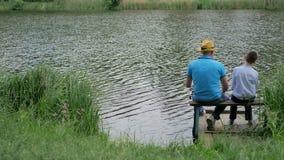 Pequeño hijo con su pesca del papá en el banco del lago almacen de video