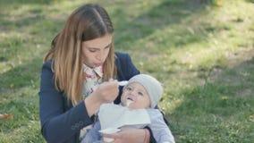 Pequeño hijo de la alimentación joven de la mamá en la naturaleza metrajes