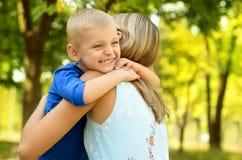 Pequeño hijo que abraza a su madre Fotografía de archivo