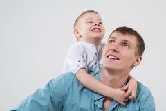 Pequeño hijo que abraza a su padre feliz Foto de archivo libre de regalías