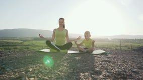 Pequeño hijo y madre que hacen yoga y la meditación del entrenamiento en al aire libre en el top de la montaña en el sol del este almacen de metraje de vídeo