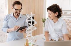 Pequeño hijo y su padre que comprueban la información sobre la DNA Imagen de archivo libre de regalías