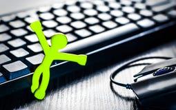 Pequeño hombre cerca del teclado y del ratón de ordenador Imágenes de archivo libres de regalías