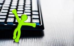 Pequeño hombre cerca del teclado y del ratón de ordenador Fotos de archivo