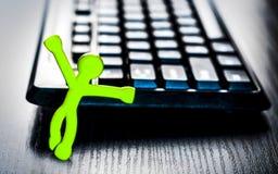 Pequeño hombre cerca del teclado y del ratón de ordenador Foto de archivo
