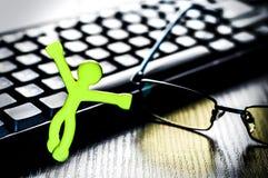 Pequeño hombre cerca del teclado y del ratón de ordenador Imagenes de archivo
