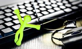 Pequeño hombre cerca del teclado y del ratón de ordenador imagen de archivo libre de regalías