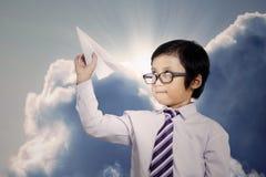 Pequeño hombre de negocios que lanza un avión de papel Foto de archivo