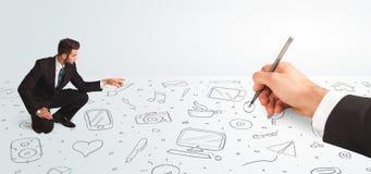 Pequeño hombre de negocios que mira iconos y símbolos dibujados as mano Fotografía de archivo libre de regalías