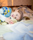 Pequeño juego caucásico de la muchacha del niño con los juguetes en la cama Imagen de archivo libre de regalías