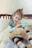 Pequeño juego caucásico de la muchacha del niño con los juguetes en la cama Imagenes de archivo