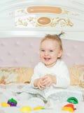 Pequeño juego caucásico de la muchacha del niño con los juguetes en la cama en casa foto de archivo libre de regalías