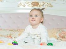Pequeño juego caucásico de la muchacha del niño con los juguetes en la cama en casa fotos de archivo