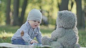Pequeño juego lindo del bebé con el oso de peluche grande almacen de video