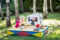 Pequeño juego lindo del bebé en salvadera de madera Niño en patio de la arena entre árboles verdes del césped y de abedul en parq Foto de archivo