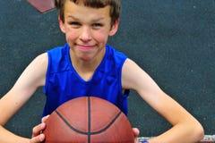 Pequeño jugador de básquet que se prepara para la bola que lanza en el cour Imagen de archivo