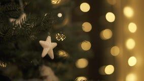 Pequeño juguete colgante de la estrella de la Navidad en árbol con las luces de la Navidad metrajes